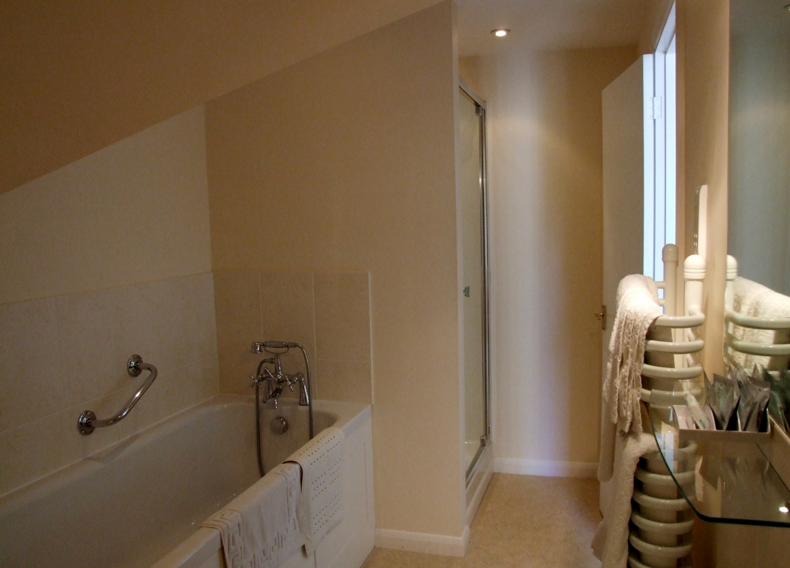 farmhouse guestroom and ensuite with both a bath and shower cubicle